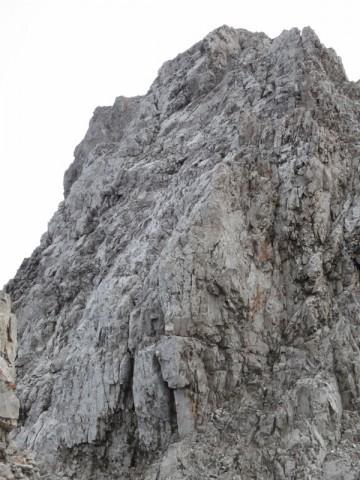 Die Schlüsselstelle im Detail; man klettert sie links (nördlich) vom Gratverlauf ab und sieht die Tritte schlecht; Seilschlupfe oben rechts leicht sichtbar