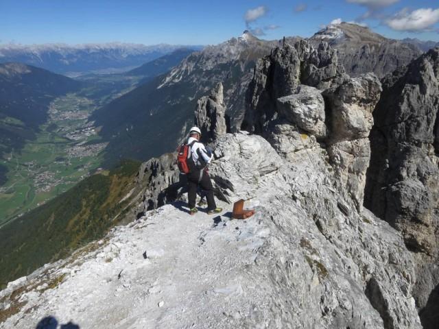 Eintrag ins Gipfelbuch der viel begangenen Route, im Hintergrund das Gipfelkreuz des Nördlichen Elferturmes