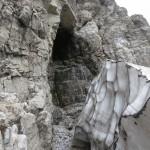 ein Schmelzbach aus einer Felshöhle unterhöhlt ein Restschneefeld