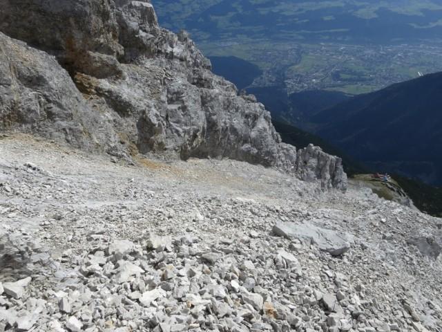 Blick über die geneigten Schuttfelder zum ersten Gratabbruch unten